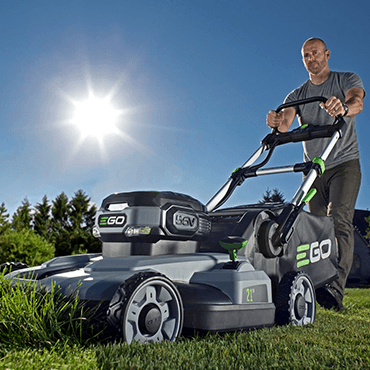 Man mowing tall grass with an EGO lawn mower.